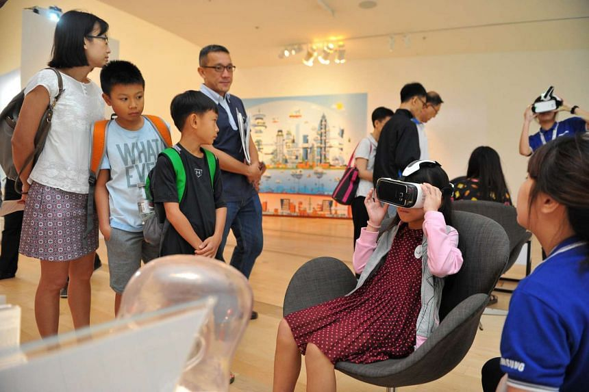 PEEK INTO THE FUTURE: The Samsung Gear VR headset showcases a vision of Singapore in 2065, drawn from public contributions as part of the #BuildSG2065 campaign. Here, nine-year-old Gwen Lee (in red), gets to experience virtual reality by using the he