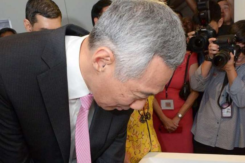 SLIDE BACK IN TIME: Prime Minister Lee Hsien Loong trying out the interactive Singapore Slider feature, which contrasts photos of old and modern-day Singapore, at the launch of the exhibition. The touchscreen table is from the ArtScience Museum's i
