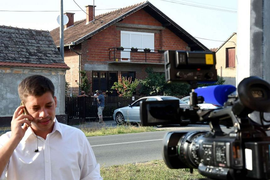 A journalist speaks on the phone in front of victim Tomislav Salopek's house (centre).