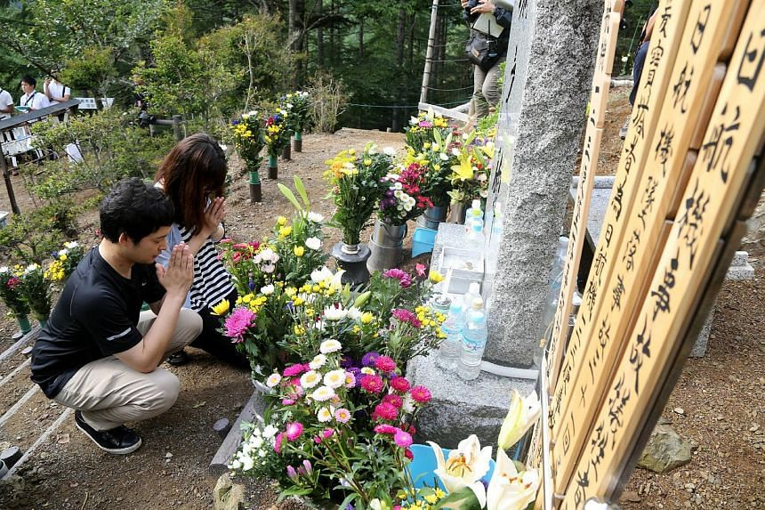 Relatives of victims of the Japan Airlines (JAL) Flight 123 crash offer prayers at a memorial for the 30th anniversary of the accident on Aug 12, 2015.