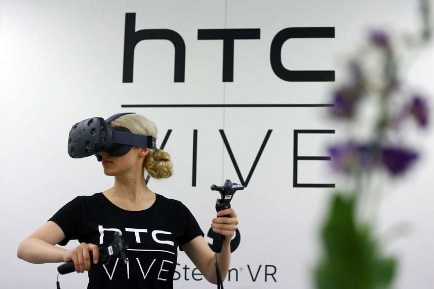 A woman tries on a pair of Vive Virtual Reality goggles, produced by Taiwan's HTC, during the Gamescom 2015 fair in Cologne, Germany, on Aug 5, 2015.