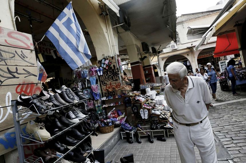 A customer browses a display of shoes for sale beneath a Greek national flag outside a store in Thessaloniki, Greece, on Aug. 11, 2015.