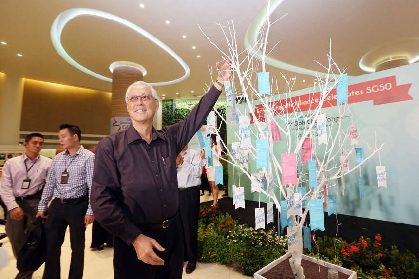 Emeritus Senior Minister Goh Chok Tong hangs up a patient's wish on the Wishing Tree at the Eastern Health Alliance SG50 celebration at Changi General Hospital on Aug 13, 2015.
