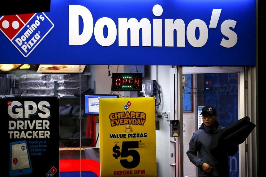 A worker carries a pizza for delivery as he exits a Domino's pizza store in Sydney, Australia, on Aug 12, 2015.