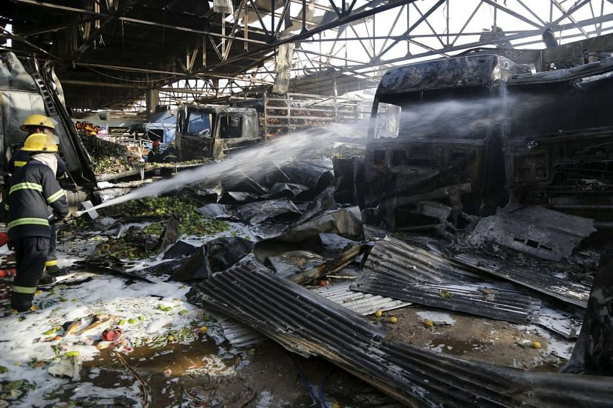 Firemen hosing down a burnt vehicle at the site of a truck bomb attack in a crowded market in Baghdad on Aug 13.