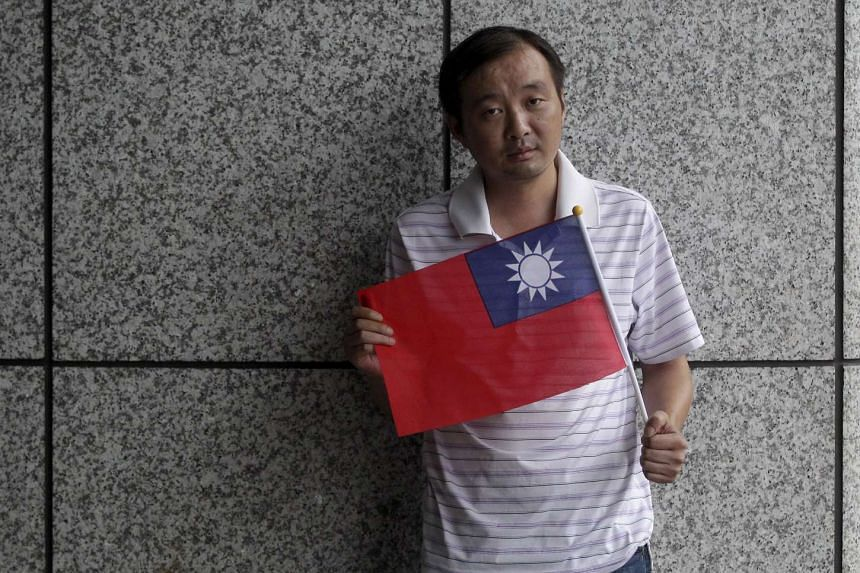 Chinese dissdent Gong Yujian poses for a photograph with a flag of Taiwan, in New Taipei City on Aug 13, 2015.