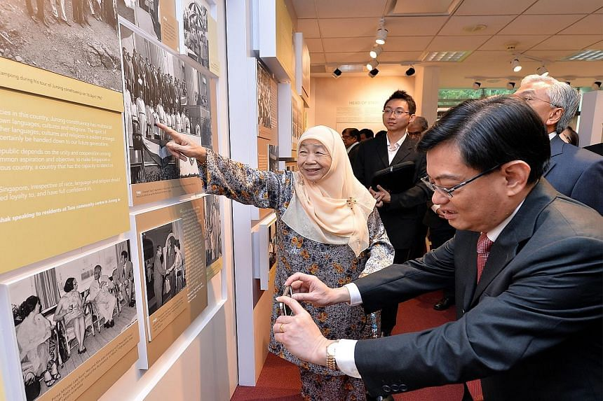 Mr Heng Swee Keat taking a photo of a panel at an exhibition on Mr Yusof Ishak's life at the Iseas library as Madam Noor Aishah, Mr Yusof's wife, points to a 1966 picture of him in ceremonial uniform. The think-tank was renamed in Mr Yusof's honour y