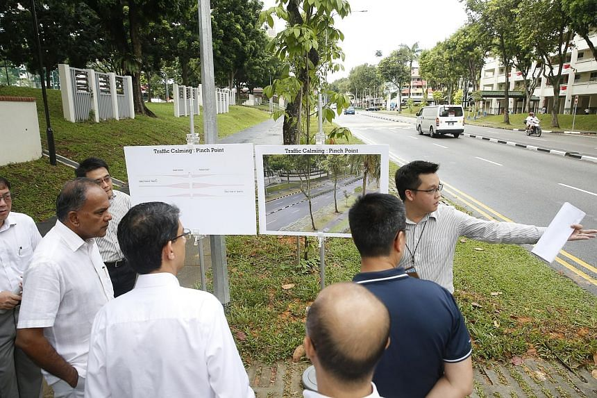 "An LTA engineer pointing out to Mr K. Shanmugam (at far left) and Associate Professor Muhammad Faishal Ibrahim (standing next to Mr Shanmugam, with back to camera) the location of the Silver Zone in Yishun Ring Road where a ""pinch point"" will be buil"