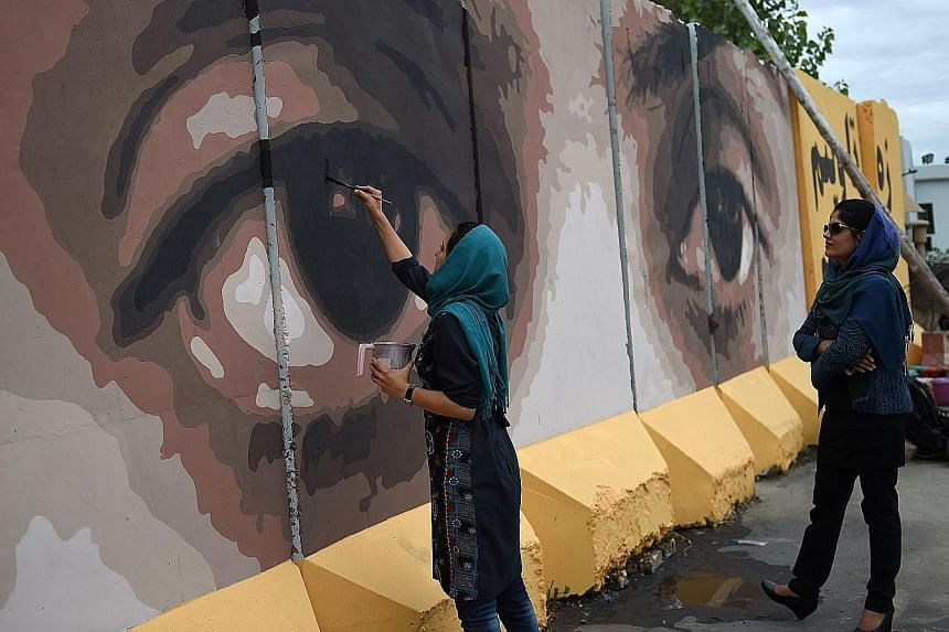 """Afghan artists and volunteers painting the eyes of a woman on a barrier wall at the presidential palace in Kabul on July 21. Alongside the eyes, a slogan reads: """"Corruption cannot be hidden from God or from the people."""""""