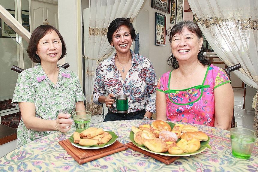 Mrs Ginger Tiah (right) with fellow Seletar Hills residents Patricia Lee (left) and Celina Gibson. Mrs Tiah oversees the production of the estate's quarterly newsletter, with the aim of building a sense of camaraderie and awareness about the estate's