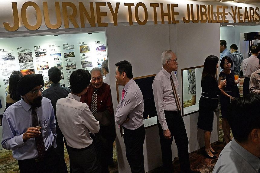 Retired pilot Kenneth Toft (right) was among a generation of transport pioneers at the Transport Ministry's SG50 gala dinner, which also featured an exhibition (above) on local transportation since independence.