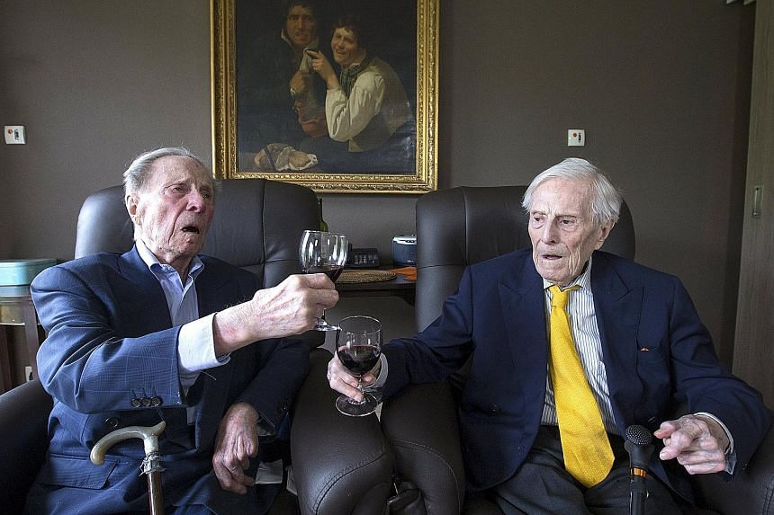 The world's oldest living twin brothers, Paulus (left) and Pieter Langerock, aged 102, toasting at the Ter Venne care home in Sint- Martens-Latem, Belgium, yesterday. Born on July 8, 1913, the Belgians never married and until this day, sleep side by
