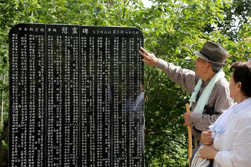 Relatives of JAL Flight 123 crash victims looking at a memorial bearing the names of those who were killed in the tragedy, at Ueno village in Gunma prefecture yesterday.