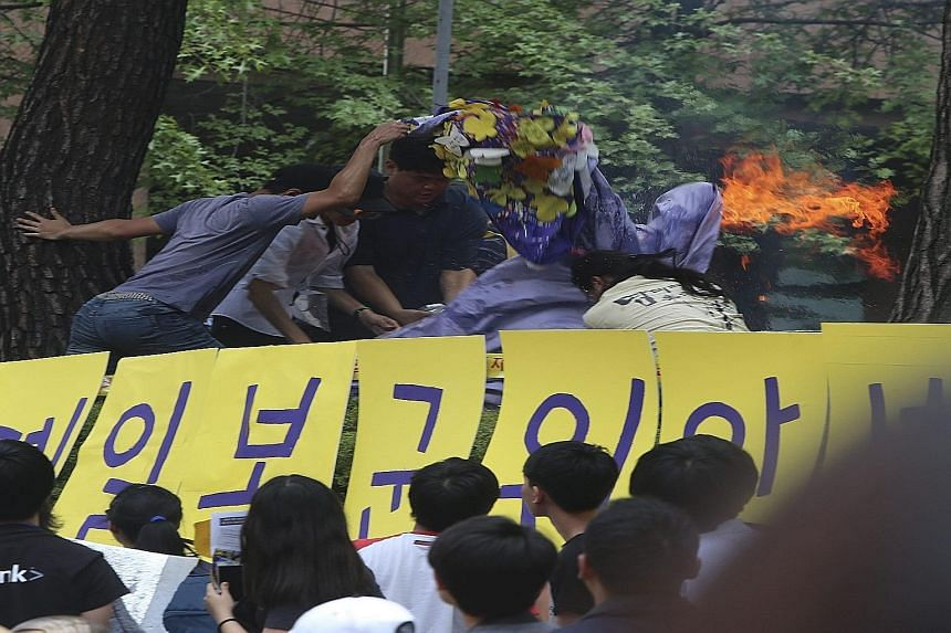 People throwing water and a blanket over Mr Choi Hyun Yeol, in a bid to extinguish the flames after he set himself on fire outside the Japanese embassy in Seoul yesterday.