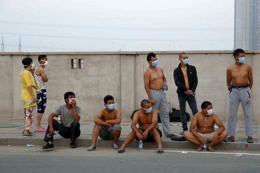 People wearing masks look on near the site of the explosions at the Binhai new district in Tianjin, China, on Aug 13, 2015.