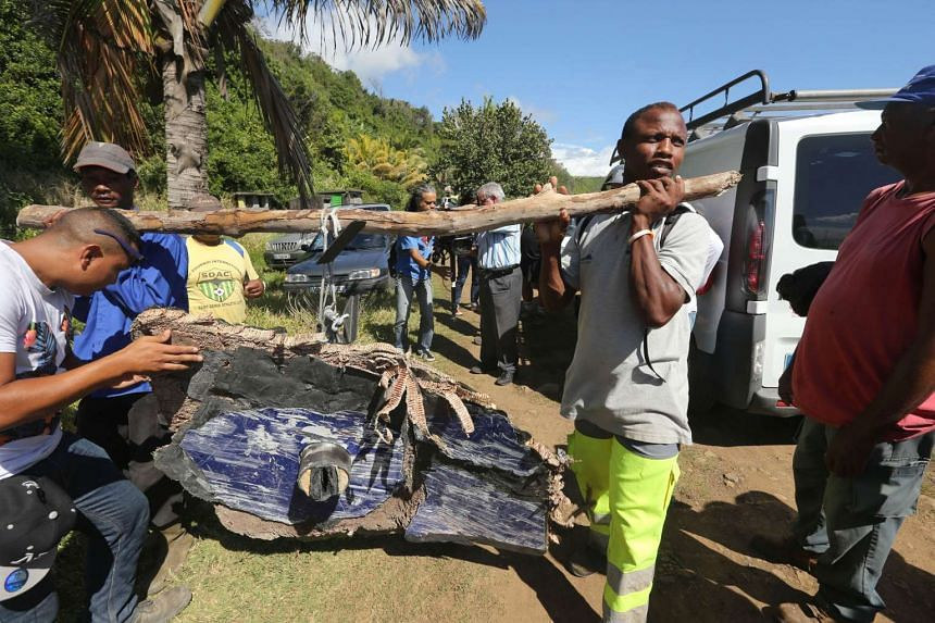 Volunteers carry debris found on Aug 11, 2015, in the eastern part of Sainte-Suzanne, on France's Reunion Island.