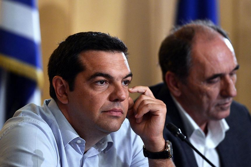 Alexis Tsipras (left) and Greek Economy Minister Giorgos Stathakis deliver a press conference after their meetings at the Greek Ministry of Infrastructure, Transport and Networks in Athens on Aug 12, 2015.