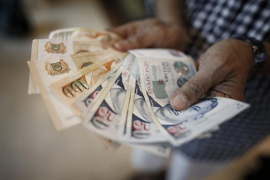 A customer displaying Singapore dollar notes at a moneychanger on Aug 12.