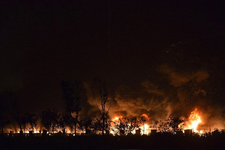 Flames and smoke rise from the site of a series of explosions in Tianjin early on Aug 13, 2015.