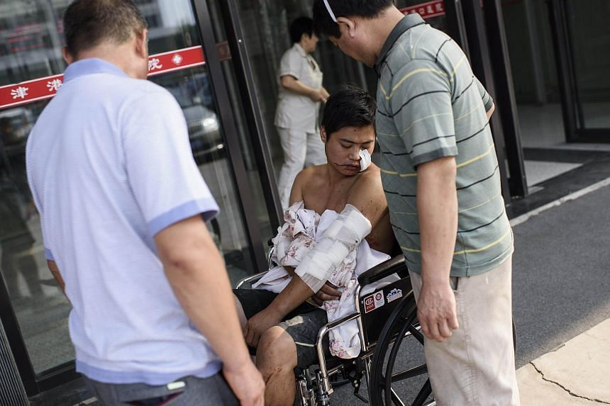 A man waits in a wheelchair after receiving treatment at Gangkou hospital in Tianjin following a series of explosions at a warehouse in the northern Chinese city on Aug 13, 2015.