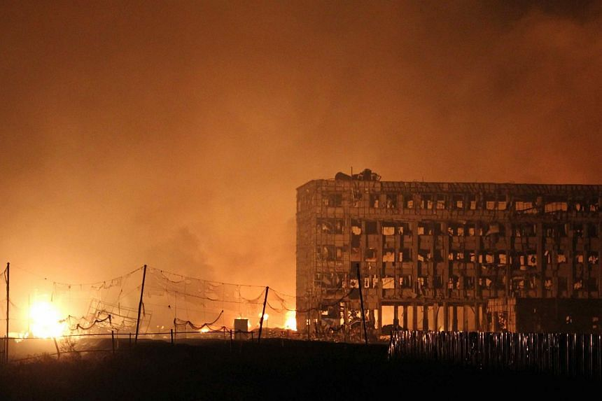 Flames rise next to a damaged building at the site of a series of explosions in Tianjin early on Aug 13, 2015.