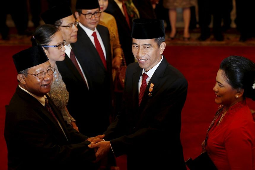 Joko Widodo (center) and his wife Iriana greet the new Coordinating Minister for Economic Affairs Darmin Nasution (left) after an oath taking ceremony at the presidential palace in Jakarta on Aug 12, 2015.