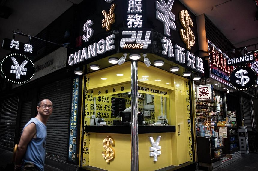 A man walking past a foreign currency exchange booth in Hong Kong on Aug 13.