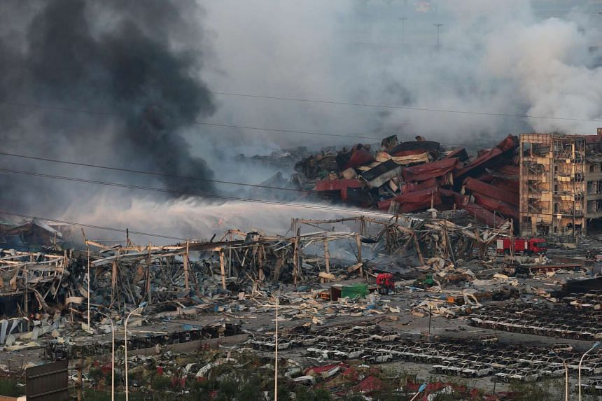 Smoke rises in the air as rescuers work among hundreds of burned cars and several destroyed buildings after a huge explosion rocked the port city of Tianjin, China, on Aug 13, 2015