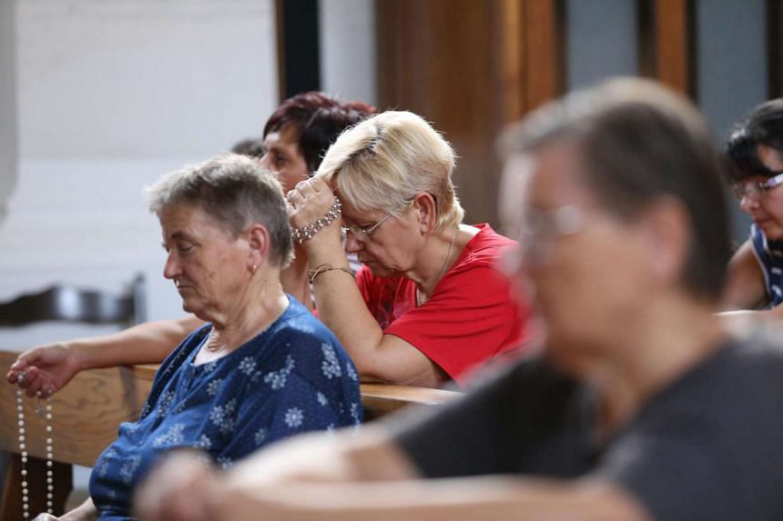Residents of Vrpolje pray in the local church on Aug 12, 2015, after hearing news that the Islamic State in Iraq and Syria claimed to have beheaded Croatian hostage Tomislav Salopek.