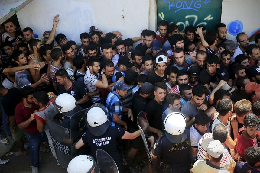 Migrants and refugees are pushed as riot police try to maintain an orderly line during a registration procedure.