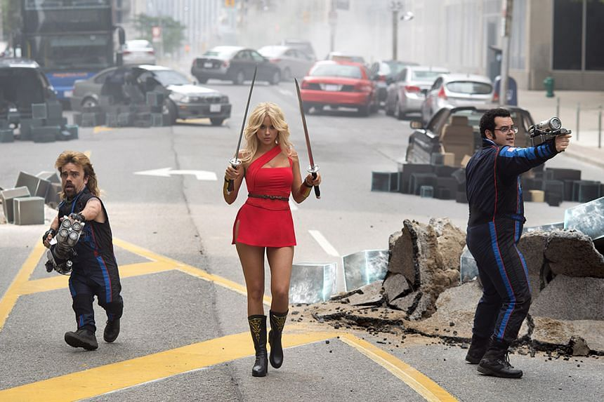 Eddie (Peter Dinklage, left) and Ludlow (right) save the world from alien invaders. Ashley Benson (middle) plays Ludlow's love interest Lady Lisa, a video game character from Dojo Quest.