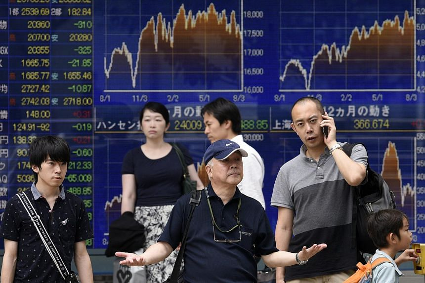 Pedestrians stand before a markets indicator board in Tokyo, Japan, Aug 12,2015.