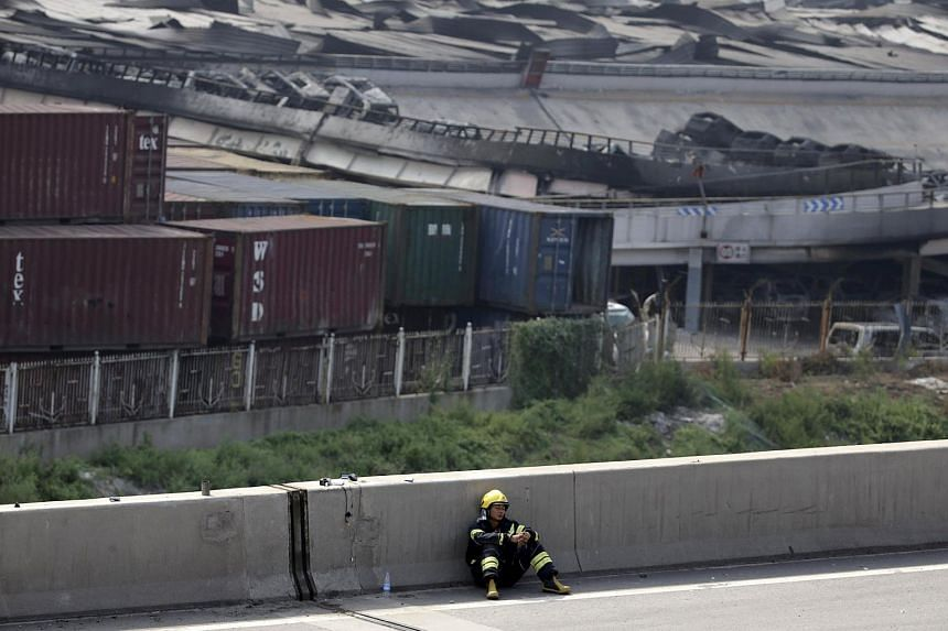 A firefighter rests on a highway next to the site of explosions at the Binhai new district in Tianjin Aug 13, 2015.