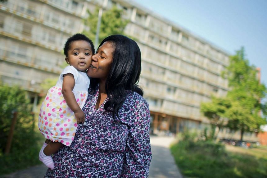 Six-month-old Angela Merkel Ade with her mother Ophelya Ade outside the Oststadtkrankenhaus refugee accommodation in Hanover, Germany on Aug 13, 2015.