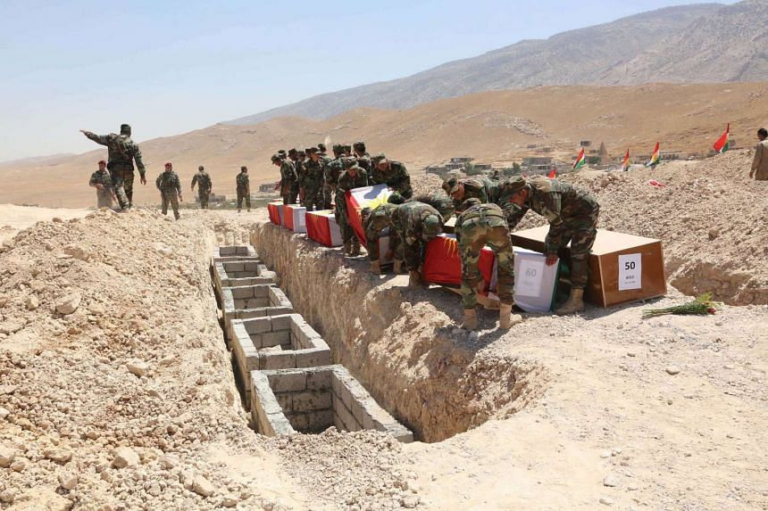 Kurdish peshmerga forces carrying coffins containing the remains of Yazidis who were killed by militants of the Islamic State, during a burial ceremony at Mazar Sharaf al-Din on Aug 13.