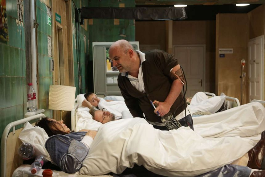 From foreground to background, actors Lili Monori (in bed), Roland Raba (standing) and Laszlo Katona (in bed furthest from camera) in a scene from Dementia, a production by Proton Theatre (Hungary) directed by Kornel Mundruczo. Part of the Singapore