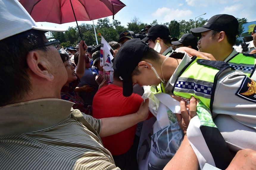 Policemen block South Korean activists who planned to launch helium balloons carrying leaflets into North Korea, in the town of Paju on Aug 14, 2015.