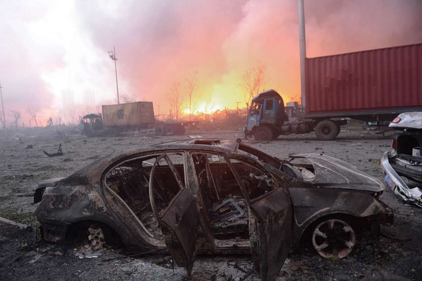 A destroyed car as a fire continues to burn after a series of explosions at a chemical warehouse hit the city of Tianjin.