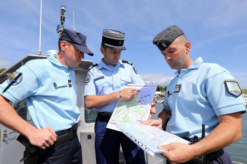 French maritime gendarmes look at a map indicating measures being undertaken in the search for wreckage from the missing MH370 plane at La Reunion on Aug 14, 2015.