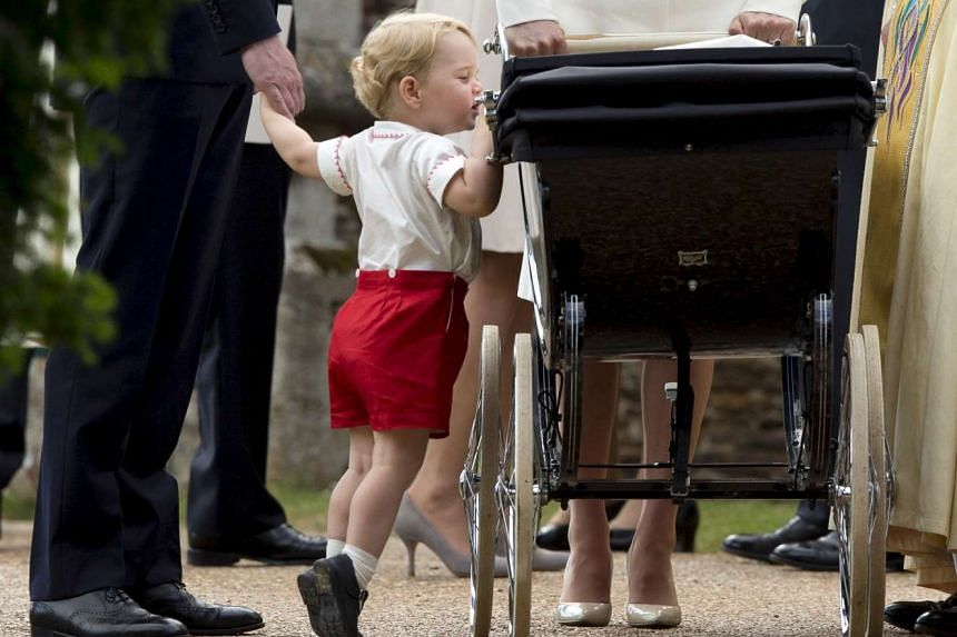 Prince George peering into his sister's pram after her christening on July 5, 2015.