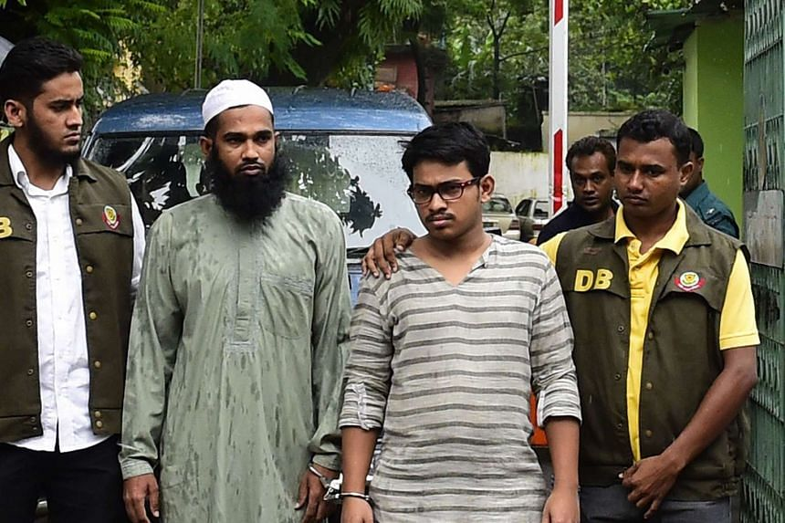 Bangladesh police officials parade suspects Masum Rana (2nd from left) and Saad-al-Nahin (2nd from right) in Dhaka on Aug 14, 2015, after their arrest in connection with the murder of secular blogger Niloy Chakrabarti, who used the pen name Niloy Nee