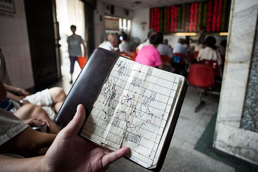 An investor studying a notebook showing stock market movements at a brokerage house in Shanghai yesterday. China's move to devalue the yuan for the third day in a row sent jitters worldwide.