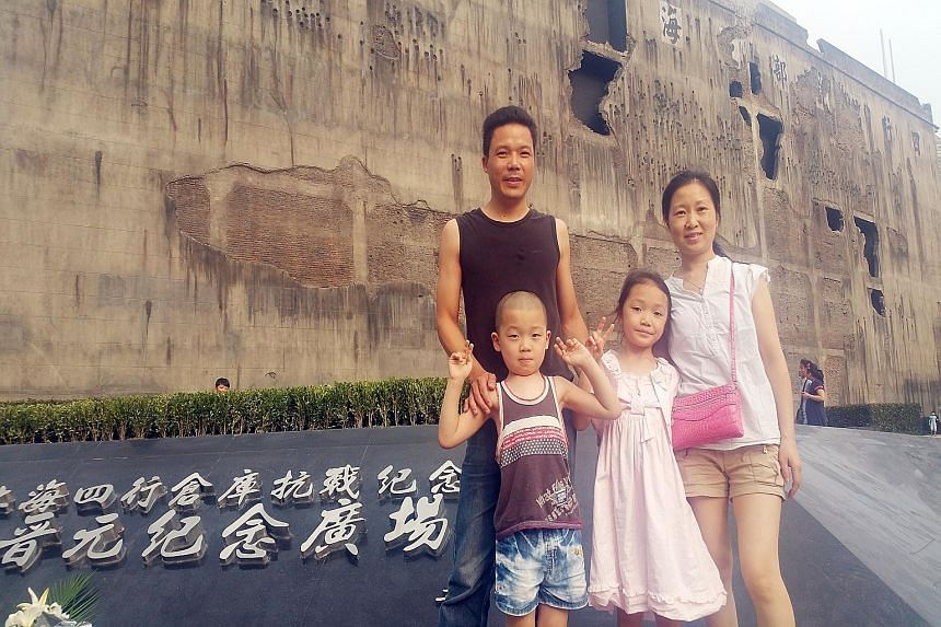 Shanghai resident Lin Yankun with his family outside the restored Sihang warehouse. Holes left by shells and bullets were recreated as part of the restoration of the battle site. Built in 1931, the Warehouse of Four Banks in Shanghai, also known as S