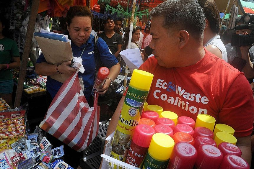 A sanitation officer (left) from the Manila Health Department (MHD) and an EcoWaste Coalition member confiscating unregistered household insecticides for sale at a shop in Manila yesterday. Members of the MHD conducted the search after claims by chem