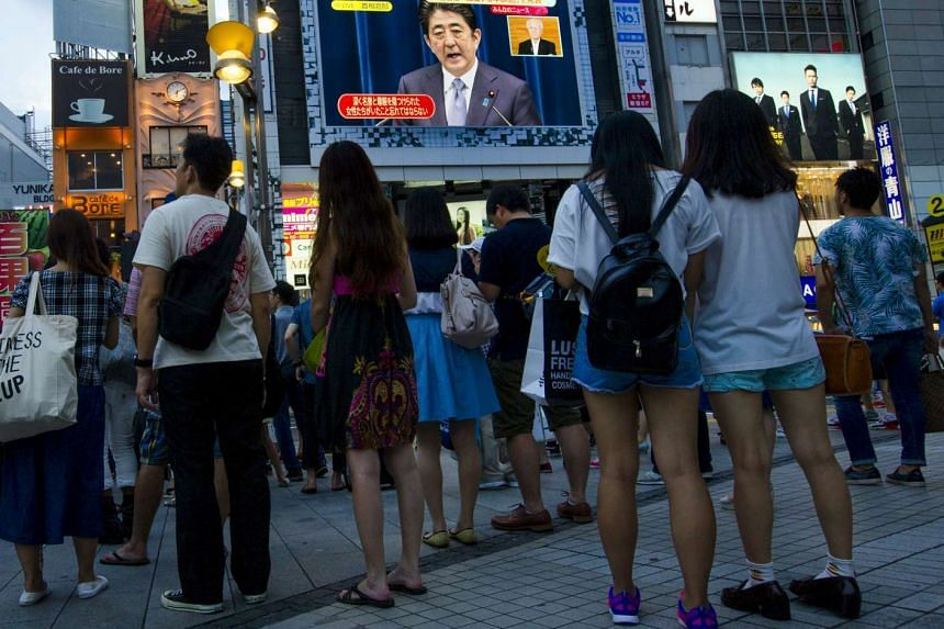 People watch Japan's Prime Minister Shinzo Abe on a screen as he gives his statement in Tokyo.