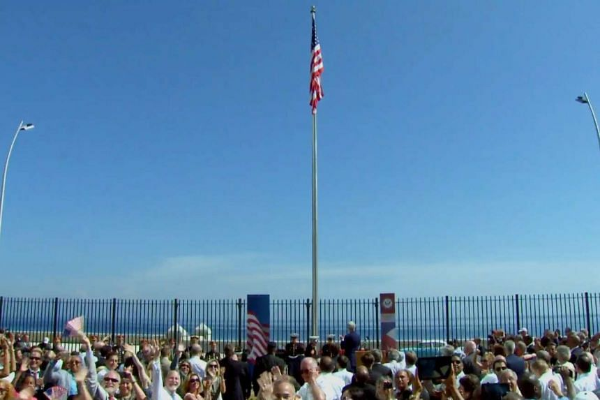 A screen grab from a US State Department video feed shows people cheering after the US flag was raised at the reinaugurated US embassy in Havana.