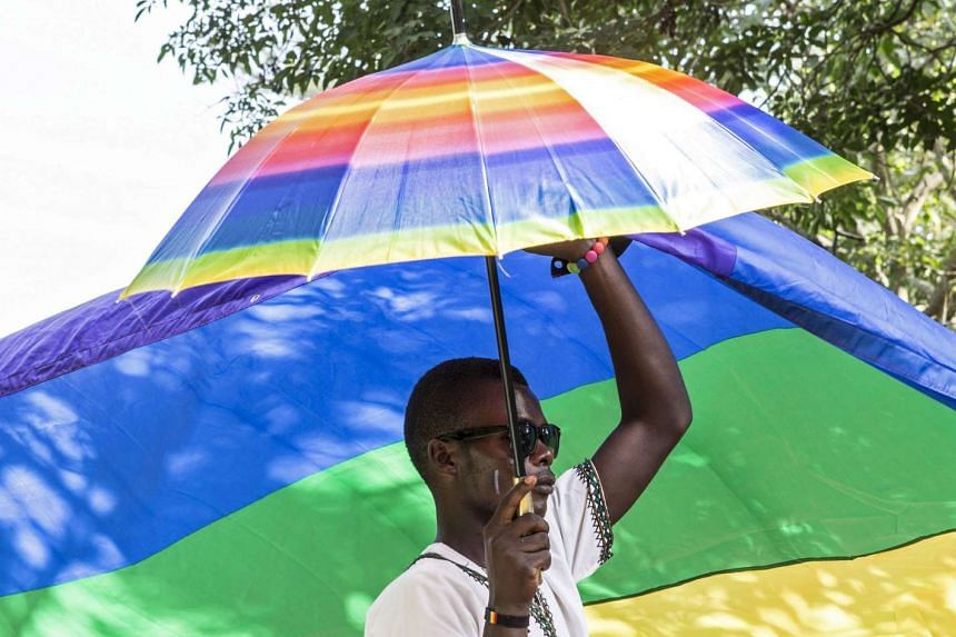 A man identifying himself as a member of LGBT community carries an umbrella at a parade in Entebbe, Uganda, on Aug 8.