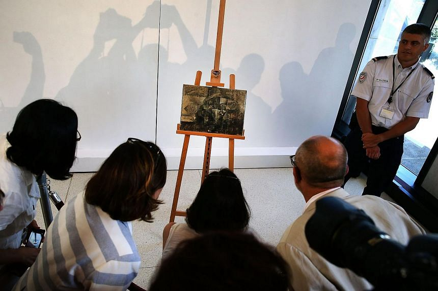 People looking at Picasso's The Hairdresser during a repatriation ceremony on Aug 13 in Washington, DC.