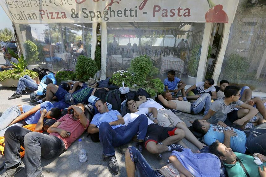 Syrian refugees rest on a street as they wait for registration outside the stadium on the Greek island of Kos.