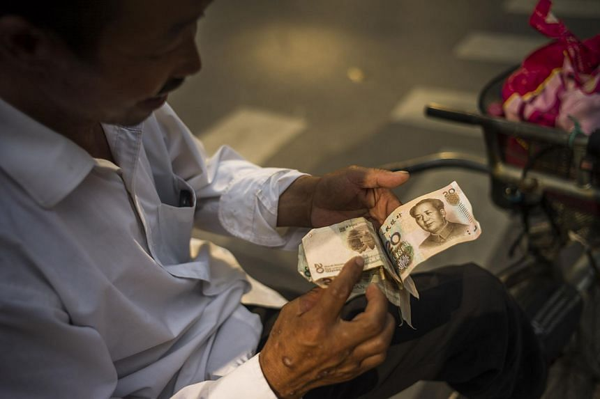 A man checking Chinese yuan bills in Beijing on July 28.